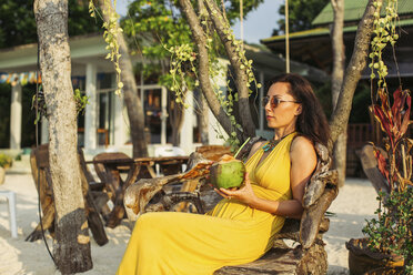 Thailand, Koh Phangan, woman sitting in a beach cafe drinking coconut water. - MOMF00397