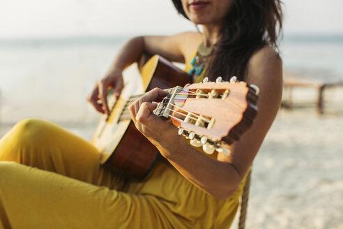 Thailand, Koh Phangan, woman playing guitar at the beach - MOMF00403