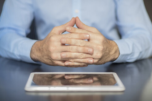 Man sitting at office desk with tablet folding hands - ZEF15100