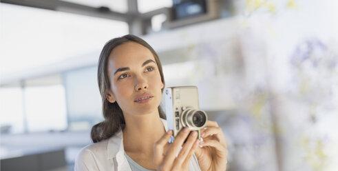 Serious brunette woman using digital camera - HOXF01028