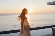 Woman in white dress on tranquil luxury patio with sunset ocean view - HOXF01040