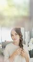 Portrait serious brunette woman braiding hair - HOXF01046