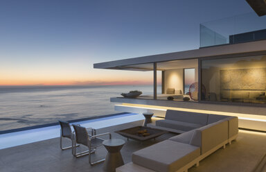 Illuminated modern, luxury home showcase exterior patio with sofa and lap pool with ocean view at dusk - HOXF01058