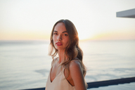 Portrait serious, beautiful woman on luxury patio with sunset ocean view - HOXF01061