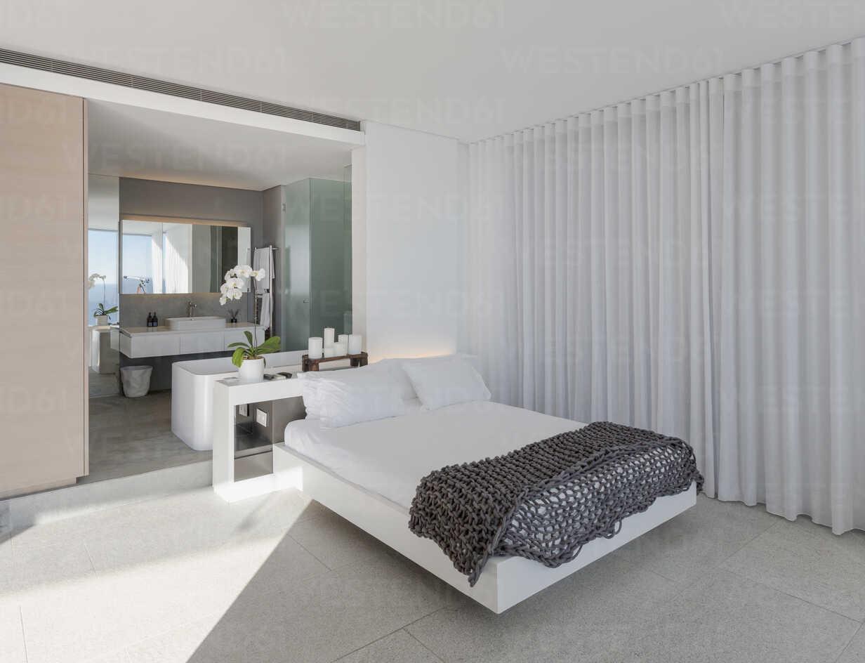 Bed in modern, luxury home showcase interior bedroom with en suite bathroom - HOXF01070 - Tom Merton/Westend61
