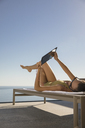 Woman sunbathing, using digital tablet on lounge chair on sunny patio - HOXF01073