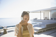 Smiling woman talking on smart phone on sunny modern, luxury home showcase exterior patio - HOXF01085