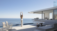 Woman practicing yoga mountain pose on sunny modern, luxury home showcase exterior patio with ocean view - HOXF01097
