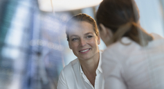 Smiling businesswoman listening to colleague - HOXF01214