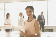 Portrait smiling, confident businesswoman with digital tablet in conference room - HOXF01238