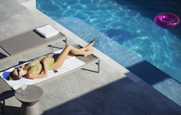 Woman in bathing suit sunbathing on lounge chair at sunny luxury poolside - HOXF01262
