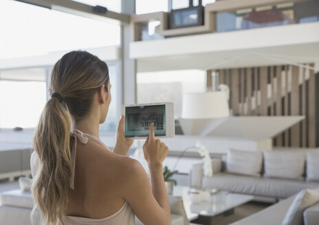 Woman with digital tablet setting digital security system in modern, luxury home showcase interior living room - HOXF01268