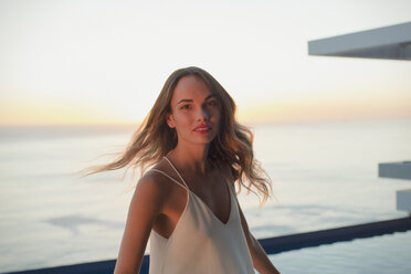 Portrait confident woman turning on luxury balcony with sunset ocean view - HOXF01280