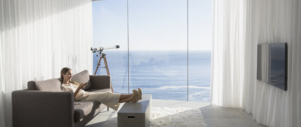 Woman relaxing with feet up, watching TV in modern, luxury home showcase interior living room with sunny ocean view - HOXF01283