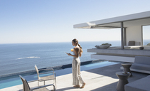 Woman walking and texting with smart phone on sunny modern, luxury home showcase patio with ocean view - HOXF01286