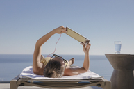 Woman sunbathing, using digital tablet on lounge chair on sunny patio with ocean view - HOXF01292