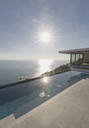 View of sun shining over ocean and modern, luxury home showcase exterior lap pool patio - HOXF01298