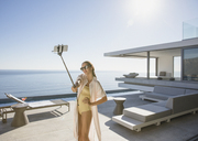 Woman in bathing suit taking selfie with selfie stick on sunny modern, luxury home showcase exterior patio with ocean view - HOXF01304