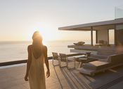 Woman walking on tranquil sunset modern, luxury home showcase exterior patio with ocean view - HOXF01310