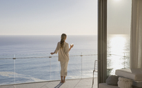 Woman standing on sunny luxury balcony with ocean view - HOXF01319