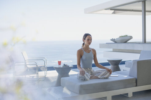 Serene woman meditating in lotus position on modern, luxury home showcase exterior patio sofa with ocean view - HOXF01322