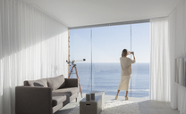 Woman with camera phone photographing sunny ocean view from modern, luxury home showcase interior living room - HOXF01328