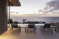 Lounge chairs on luxury patio with sunset ocean view - HOXF01343