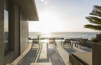 Lounge chairs on sunny luxury patio with ocean view - HOXF01349