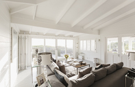 Sunny luxury home showcase living room with white wood beam vaulted ceiling - HOXF01370