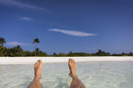 Personal perspective barefoot man floating in tropical ocean surf with view of beach - HOXF01424