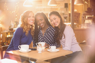Portrait smiling women friends drinking coffee at cafe table - HOXF01457