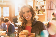 Portrait smiling woman drinking iced coffee in cafe - HOXF01487