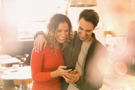 Affectionate couple using cell phone in cafe - HOXF01493