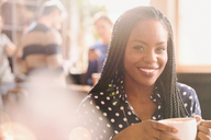 Portrait smiling African woman drinking cappuccino in cafe - HOXF01502