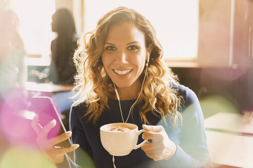 Portrait smiling woman with headphones listening to music on mp3 player and drinking cappuccino in cafe - HOXF01517