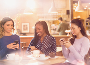 Women friends texting with cell phones at cafe table - HOXF01559