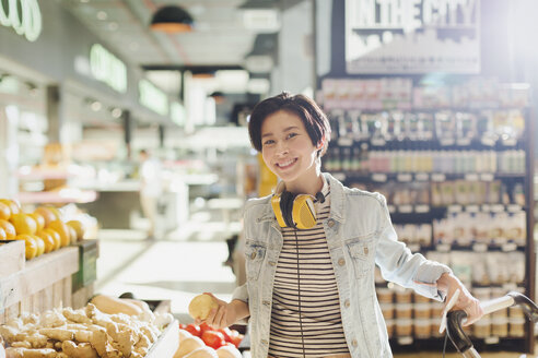 Portrait smiling, confident young woman with headphones grocery shopping in market - HOXF01607