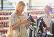 Smiling young woman texting with cell phone at grocery store market checkout - HOXF01616