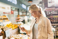 Young woman using cell phone in grocery store market - HOXF01640