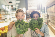 Portrait playful young lesbian couple holding fresh kale in grocery store market - HOXF01643