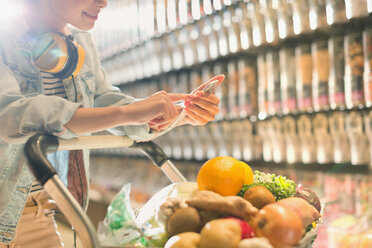Young woman with headphones using cell phone, grocery shopping in market - HOXF01661