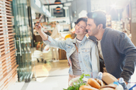 Young couple taking selfie grocery shopping in market - HOXF01664