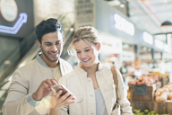 Smiling young couple using cell phone in grocery store market - HOXF01676