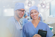 Portrait smiling, confident surgeons with digital tablet in operating room - HOXF01712
