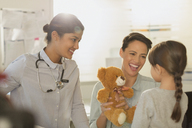 Smiling female pediatrician and mother showing teddy bear to girl patient in examination room - HOXF01733