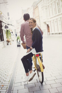 Portrait smiling woman riding on back of boyfriend's bicycle on city street - HOXF01817