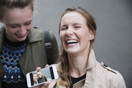 Laughing young women showing selfie photograph on smart phone - HOXF01823