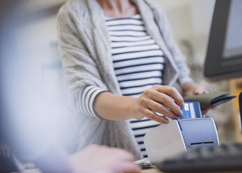 Woman using credit card reader in shop - HOXF01826