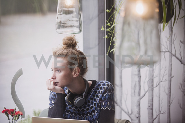 Pensive young woman with headphones at laptop looking out cafe window - HOXF01835