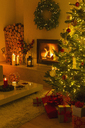 Ambient fireplace and candles illuminating living room with Christmas tree and decorations - HOXF01859